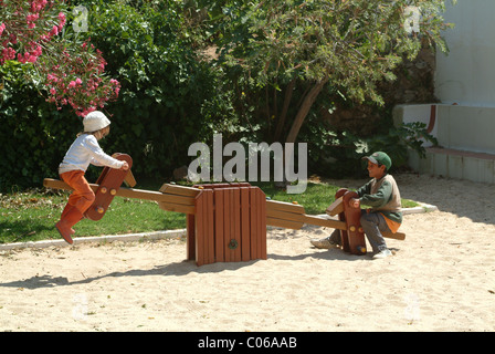A Young Girl and Boy Playing on a See-saw in a Playground in a Park in Alvor Algarve Portugal Europe - Stock Photo