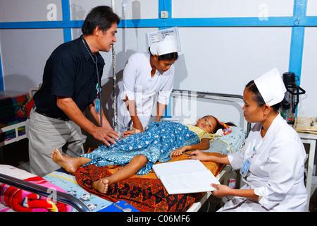 Ward round, girl lying in a hospital bed, hospital, Balinge, Batak region, Sumatra island, Indonesia, Asia - Stock Photo