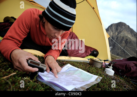 Woman in a tent consults a GPS and map while camping at Rabbit Lake, Chugach State Park, Southcentral Alaska, Autumn - Stock Photo