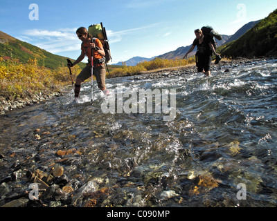 Two female hikers with walking sticks crosses Windy Creek along the Sanctuary River Trail in Denali National Park, - Stock Photo