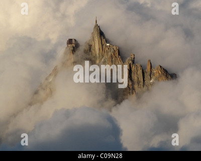 The Aiguille du Midi pokes through the clouds just before sunset. - Stock Photo
