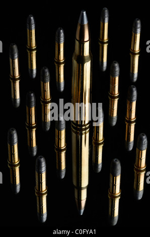 Full metal jacket Winchester 30 06 Springfield cartridge and 22 calibre lead rifle bullets on black mirror - Stock Photo