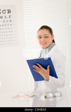 Optician doctor woman with prescription glasses and eye chart - Stock Photo