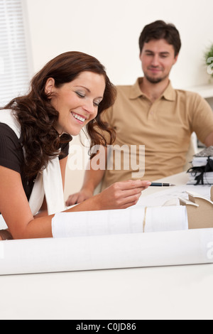 Smiling man and woman with architectural model at office - Stock Photo
