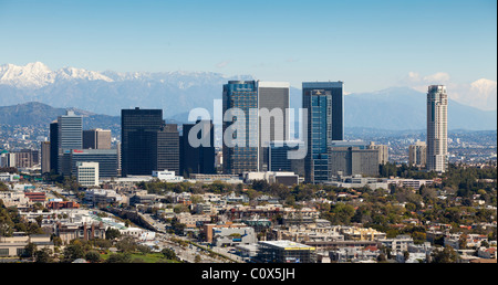 Skyline of Century City area of Los Angeles after a winter storm featuring snow on mountains in background. - Stock Photo
