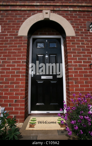 Front door to a house with a welcome door mat - Stock Photo