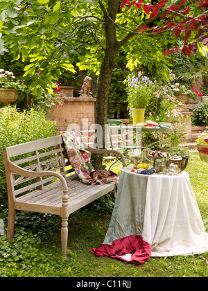 Old garden bench with a nicely laid table, romantic ambience - Stock Photo