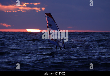 Surfer in front of the sunset, Baltic Sea, Ruegen, Mecklenburg-Western Pomerania, Germany, Europe - Stock Photo