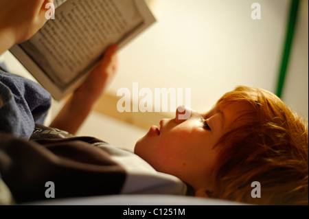 Child, boy reading in bed - Stock Photo
