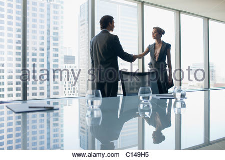 Business people shaking hands in conference room - Stock Photo