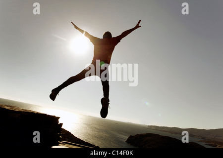 Man leaping through the air by the sea - Stock Photo