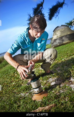 Young man prepares a gas burner at a campsite on the banks of Shelby Lakes in Gulf Shores Alabama. - Stock Photo