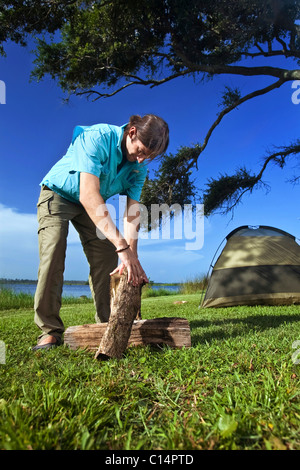 Young man stack wood at a campsite on the banks of Shelby Lakes in Gulf Shores Alabama. - Stock Photo