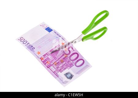 From an Euro banknote a piece is cut with scissors. Symbol taxes and fees. - Stock Photo