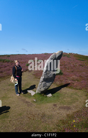 Teenage girl standing beside the bronze age standing stone known as the Old Man of Gugh, St Agnes Isles of Scilly - Stock Photo