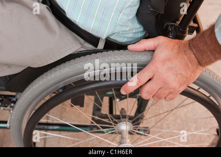 Man with spinal cord injury sitting in a wheelchair - Stock Photo