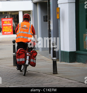 Postman riding a bicycle with pannier bags on his town centre round in Evesham England UK - Stock Photo