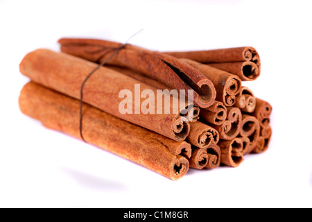 View of a bunch of cinnamon spice quills isolated on a white background. - Stock Photo