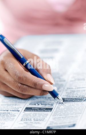 Black female hand circling ad in newspaper classified section looking for job - Stock Photo