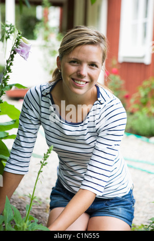 Portrait of young woman in backyard - Stock Photo