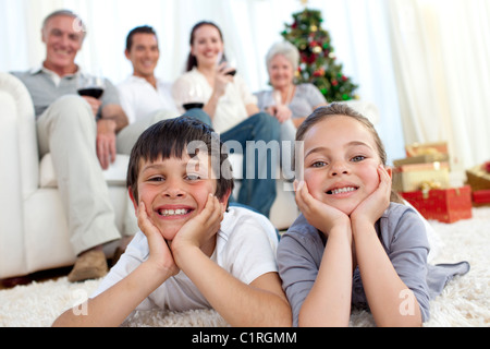 Brother and sister on floor with their family in Christmas - Stock Photo