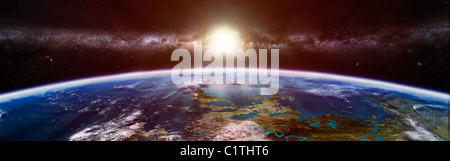 Artist's concept of an extraterrestrial planet showing the Sun and a galaxy on the horizon. - Stock Photo