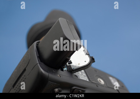 Inserting a lithium battery into a digital SLR camera - Stock Photo