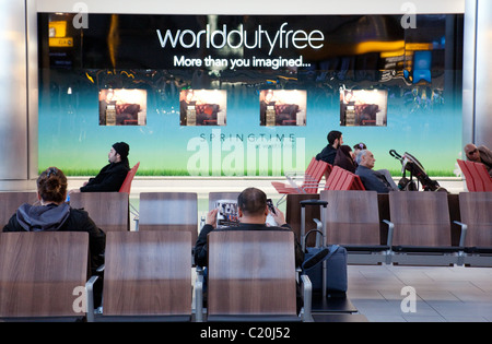 Passengers in the departure lounge against the backdrop of the World Duty Free store, Terminal 5, Heathrow airport, - Stock Photo