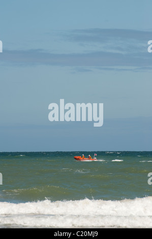 RNLI lifeboat speeding along the coast. - Stock Photo