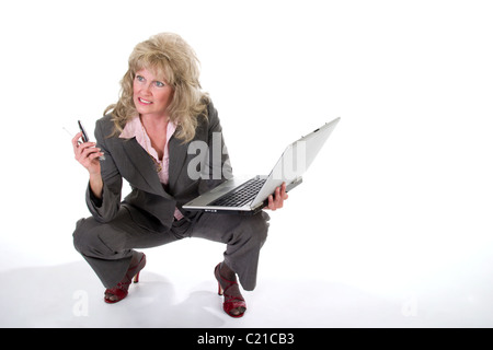 Attractive business trying to work on her laptop while dealing with her cellphone - Stock Photo