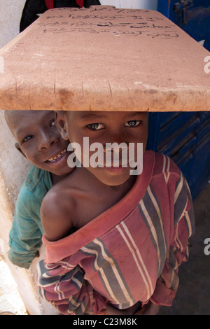 Schoolboy carrying writing tablet on his head in the Kibédoué quarter of Bobo Dioulasso - Stock Photo