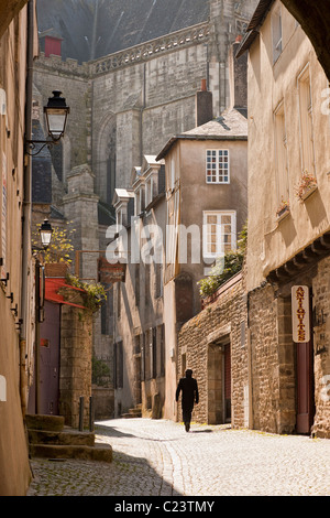 Man walking away down an ancient old cobbled medieval street in Vannes, Brittany, France, Europe - Stock Photo