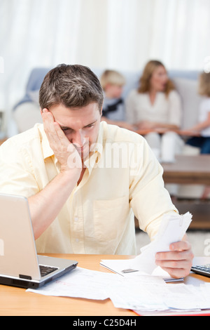 Man calculating his bills while his family are on the sofa - Stock Photo