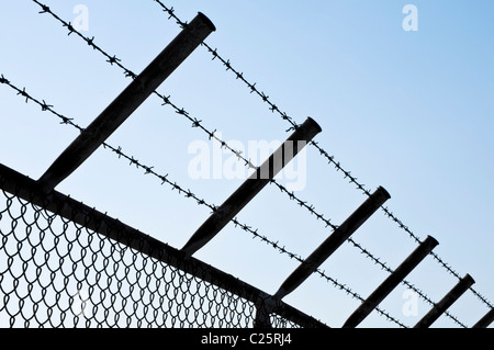 Silhouette of a Barbed Wire Fence against clear Sky - Stock Photo