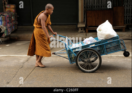 young novice monk pushing cart with food collecting on morning alms round , mae sot, northern thailand - Stock Photo
