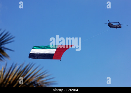 Military helicopter carries the national flag of the United Arab Emirates over the capital  Abu Dhabi. During a - Stock Photo