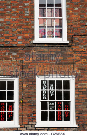 Looking up at a Barber's shop windows and the signs within at Blandford Forum in Dorset, England - Stock Photo