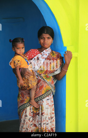 Indian mother with child on blue and yellow door way Andhra Pradesh South India - Stock Photo