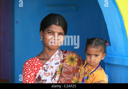 Indian mother with child on blue and yellow door Andhra Pradesh South India - Stock Photo