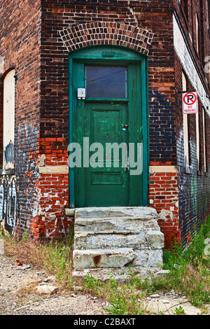 Entrance to Abandoned Building with Green Door, Pealing Paint and Crumbling  Stairs. - Stock Photo