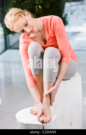Young woman massaging feet - Stock Photo