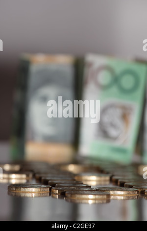 Australian Gold Coins in Focus in Front of One Hundred Australian Paper Notes - Stock Photo