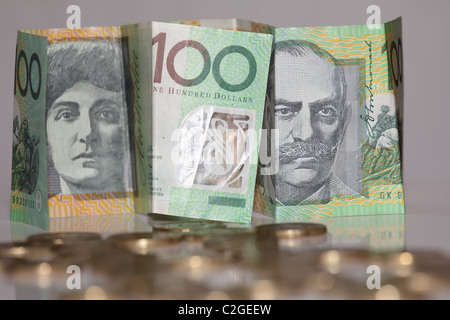 One Hundred Australian Paper Notes in Focus with Gold Coins in Foreground - Stock Photo