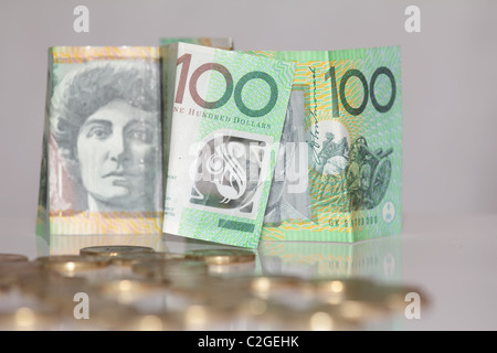 One Hundred Notes in Focus in front of Australian Gold Coins - Stock Photo