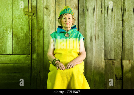 86 years stylish woman is sitting on the chair. Looking in front of the camera. - Stock Photo