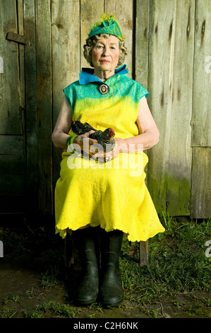86 years stylish woman is sitting on the chair. Looking in front of the camera and  holding the chicken. - Stock Photo