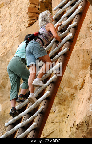 People climbing a wood ladder along a dwelling of Balcony House, cliff dwelling in Mesa Verde National Park - Stock Photo