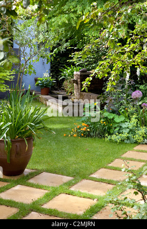 Suburban Garden. Agapanthus in large pot on checkerboard stone and grass paving - Stock Photo
