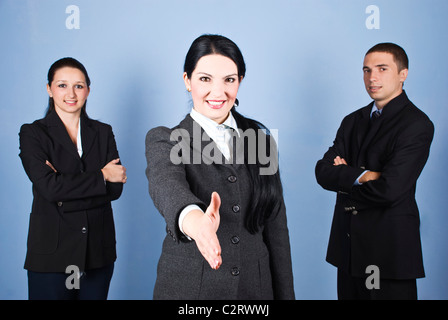 Three business people team standing and smiling for you with a businesswoman in front of image giving hand shake - Stock Photo