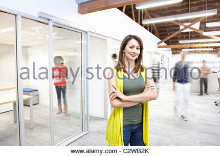 Busy people walking past businesswoman in office - Stock Photo